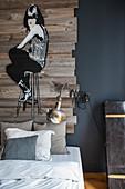 Graffito auf alten Brettern über dem Bett an grauer Wand