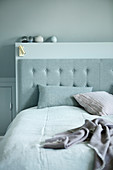 Button-tufted bed headboard against partition wall below sloping ceiling