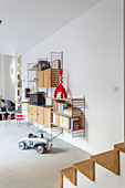 Toy car on floor below designer string shelving