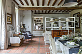 Dining area with terracotta floor riles, wood-beamed ceiling, chest of drawers and partition screen in rustic interior