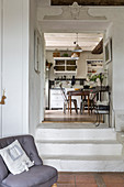 Easy chair with scatter cushion in front of open doorway leading into kitchen