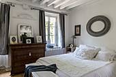 Doppelbett und antike Kommode in rustikalem Schlafzimmer