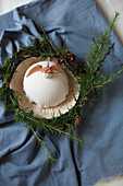 Angel on textured dish in wreath of larch twigs