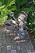 Old zinc watering cans and planted sieve on cobbles
