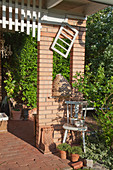Brick pillar with aperture and rustic arrangement of potted plants and chair on terrace
