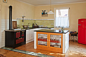 Island counter with glass cupboard doors in open-plan kitchen with antique cooker