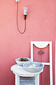 Bowls on table and white window frame against deep pink exterior wall