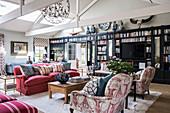 Wohnzimmer im Englischen Stil mit offener Decke und Bücherwand