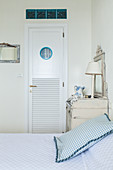 Door with porthole and transom window made from glass bricks in bedroom