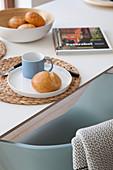 Teller mit blauer Tasse und Semmel auf Korbuntersetzer auf Frühstückstisch