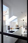 Blick durch Glastür in weiße Einbauküche