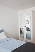 Einzelbett und Kleiderschrank mit Spiegeltür im Gästezimmer