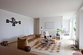 Hellbraune Ledercouch, Couchtisch, Sitzpouf und Drehstuhl im Wohnzimmer