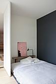 Bett und Bank in schlichtem Schlafbereich mit grau-blauer Wand