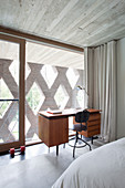 Desk in bedroom with glass wall and perforated façade