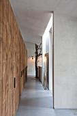 Einbauschränke aus rauem Holz im Flur mit Betonboden