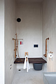 Toilet integrated into bench and bidet shower in narrow bathroom