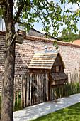Hühnerhaus aus Holz an einer Gartenmauer aus Backstein