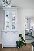 Old dresser painted white with glass-fronted top cabinet