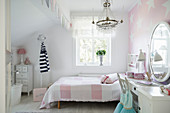 White and pink girl's bedroom with star-patterned wallpaper on wall behind bed