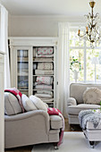 Blankets in lovely old glass-fronted cabinet in living room