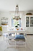 Bank und Stühle um den weißen Tisch im nostalgischen Esszimmer