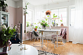 Delicate metal chairs around dining table in front of pink wall