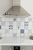 Extractor hood over cooker with hob cover and white and blue wall tiles in kitchen