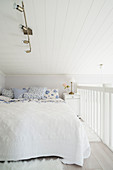 Double bed with white bedspread and white and blue scatter cushions on gallery