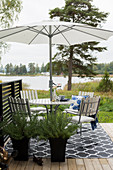 Round table with parasol and chairs on terrace with view of lake