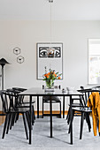 Dining table and chairs below pendant lamp and in front of poster on wall