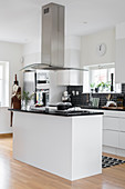 Black tiled splashback and extractor hood above island counter in white kitchen