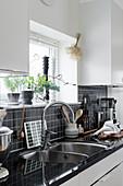 weiße Küche mit schwarzem Fliesenspiegel