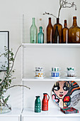 Green and brown bottles and china on String shelves in kitchen