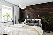 Wall clad in dark wood in wintry bedroom