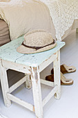 Summer hat on old stool with peeling paint next to bed