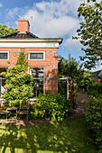 Summery garden around small brick house