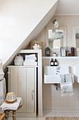 Beige bathroom with cabinet below sloping ceiling