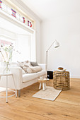 White sofa, standard lamp and wicker coffee table in front of window bay