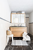 Waschbeckenunterbau mit Holzfront und Spiegelschrank im Bad mit schwarzen Marmor-Bodenflliesen