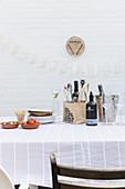Tisch mit Zutaten für Vorspeise und Getränken vor weißer Wand auf der Terrasse