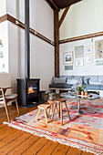 Wooden stools and coffee table on ethnic rug in front of pallet sofa