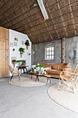 Wohnzimmer mit Korbmöbeln und Pflanzen in einer alten Scheune