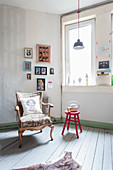 Baroque armchair and red stool used as side table below gallery of pictures
