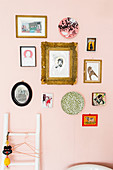 Gallery of pictures, postcards and decorative wall plates on pink wall
