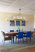 Chairs with blue upholstery and rattan armchairs around wooden table in dining room