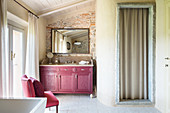 Claret-red washstand cabinet and chair in Mediterranean bathroom