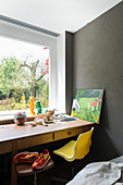 Schreibtisch mit Katze vor Fenster, Drehhocker und gelber Schalenstuhl