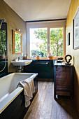 Badewanne, antik Kommode und Waschbecken im Badezimmer mit Fenster und Holzdielenboden