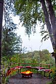 Bank und Feuerschale auf einer Naturterrasse mit aufgehängten, DIY-Sommerlichtern aus Metalldosen